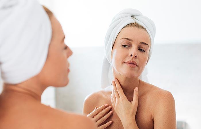 Mujer revisando su piel en el espejo