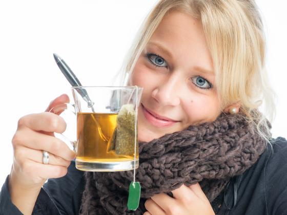 Chica enferma con té verde en mano