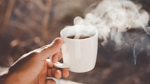 Mano con taza de café