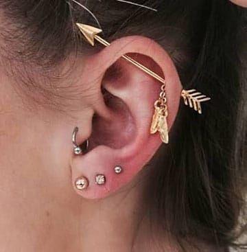 Chica con diferentes aretes en su oreja