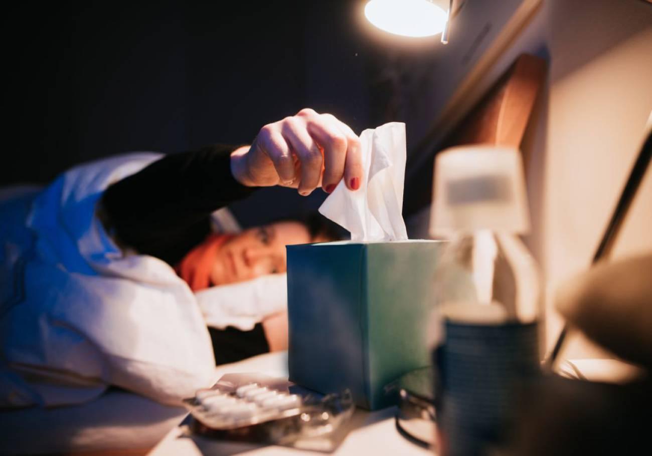 Mujer con gripe en cama