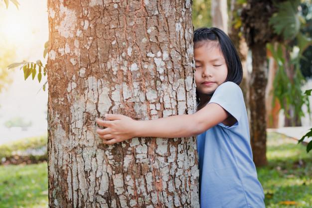 Niña abrazando un árbol