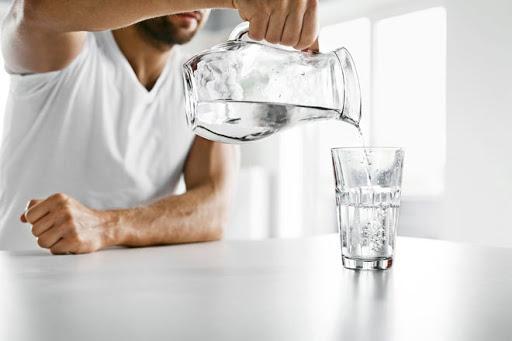 hombre sirviendo vaso de agua