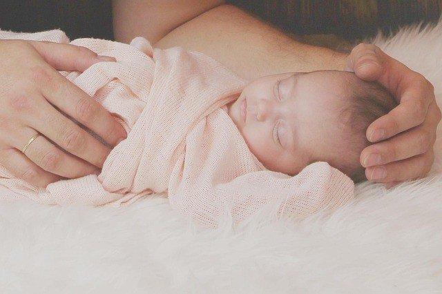 Bebé dormido en brazos de su mamá
