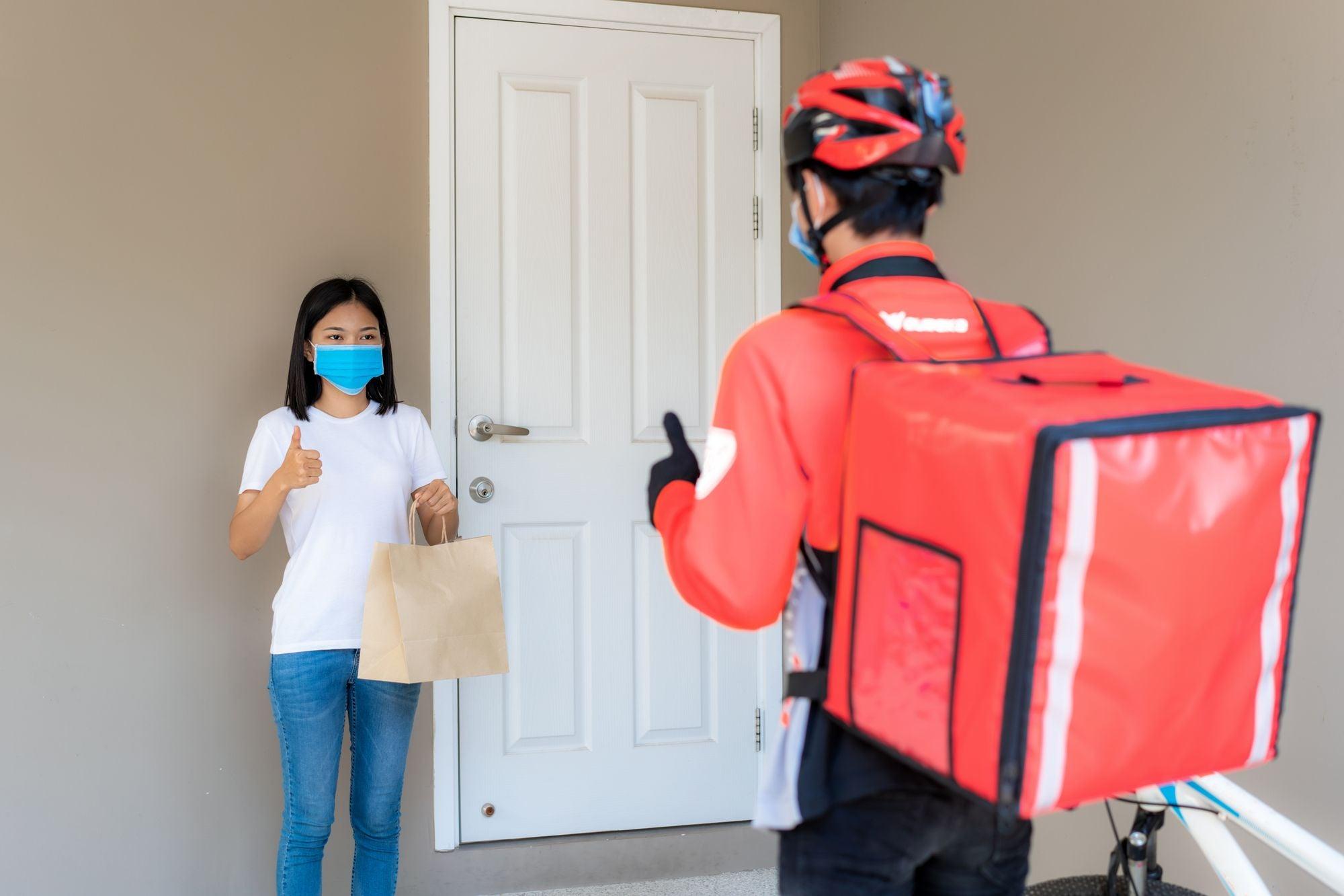 mujer recibiendo comida por servicio a domicilio